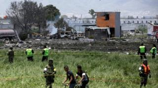 Soldiers and police officers keep watch at a site damaged due to fireworks explosions in the municipality of Tultepec, on the outskirts of Mexico City, Mexico July 5, 2018.