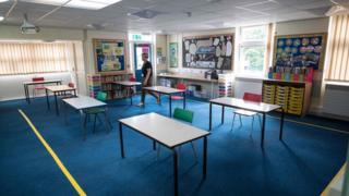 A headteacher in an empty classroom