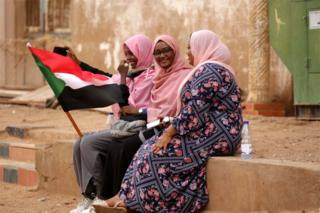 Three women wearing pink hijabs chat and smile. They are sitting on a raised pavement and only of them is holding a Sudanese flag.