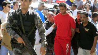 Flemngo goalkeeper Bruno Fernandes being escorted by police in 2010