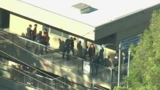 ตำรวจตรวจค้นนักเรียนขณะที่อพยพออกมาจากห้องเรียน
