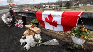 A woman adjusts flowers at a makeshift roadside memorial for Royal Canadian Mounted Police Constable Heidi Stevenson
