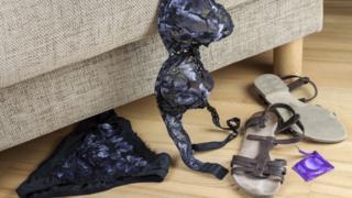 Ropa interior de mujer y sandalias al lado de un mueble.