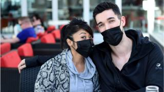A couple prepares for air travel with masks, hand sanitiser and wipes