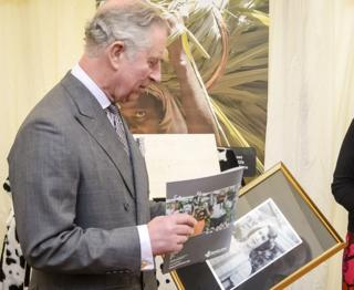 The Prince Of Wales studies the black and white photograph of The Queen