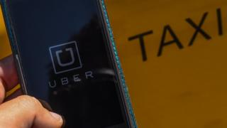 In this photo illustration, the new smart phone app 'Uber' logo is displayed on a mobile phone next to a taxi on July 1, 2014