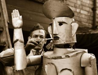 15th January 1939: Mr Charles Lawson, an electrical engineer of Kettering lights his robot's cigarette