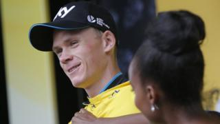 "Britain""s Chris Froome gets his yellow jersey adjusted. It shows he's the leader of the Tour De France."