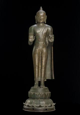 A bronze Buddha statue with a flame on top of the head that symbolises wisdom.