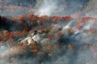 Smoke surrounds a home as seen from aboard a National Guard helicopter near Gatlinburg, Tennessee