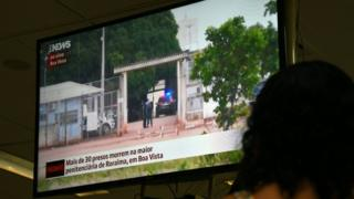A woman watches on television news about the riot in the PAMC (Agricola de Monte Cristo Penitentiary) in Roraima, northern Brazil