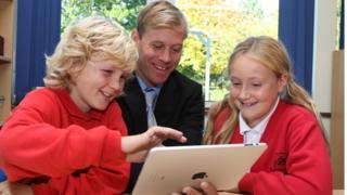 Professor (ao centro) recebe ensinamentos de um garoto (esq.) e uma menina (dir.) em um tablet