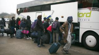 Refugees wait to board a bus