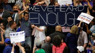 支持者集会の中でも「もうたくさんだ」などと横断幕を掲げて抗議する人たち(24日)