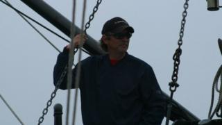 Joseph Howlett pictured aboard a ship, wearing sunglasses and a hat