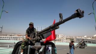مسلح من الحوثيين يجلس على سيارة ذات دفع رباعي مزودة بمدفع