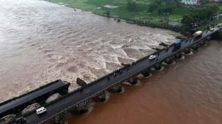 In this photograph released by The Indian Coast Guard on August 3, 2016, bystanders look at the partially collapsed bridge over the River Savitri in Raigad District some 100kms from Mumbai
