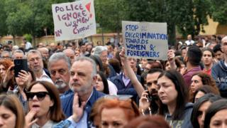 Protesters hold placards at a vigil to commemorate the victims of the serial killer in Nicosia on April 26