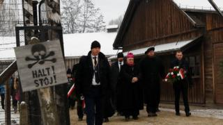 """People arrive to lay wreaths at the """"death wall"""" at the former Nazi German concentration and extermination camp Auschwitz"""