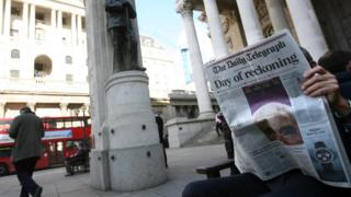 Man reads newspaper outside the Bank of England
