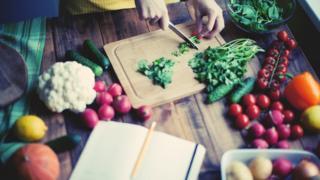 Mulher cortando produtos de origem vegetal