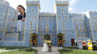 Lego figures of Britain's Prince Harry and Meghan Markle pose in front of a model of Windsor Castle