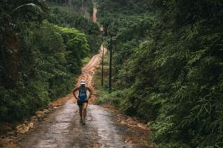 Mina Guli treks up a muddy path near the Amazon River in Brazil