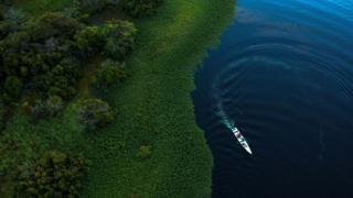 Foto mostra área de floresta e rio, pelo qual passa um pequeno barco, em vista aérea