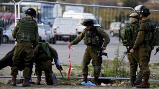 Israeli soldiers pick up debris and bloodied pieces at the scene of the attack near Gush Etzion.