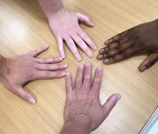 Four people lay their hands on a table
