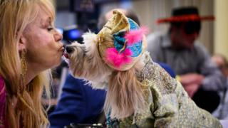 A woman kisses her dog dressed in a sultan costume