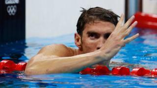 Michael Phelps faz o número quatro com os dedos, indicando ser o único tetracampeão na mesma prova olímpica