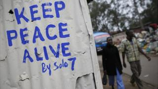 "Pedestrians walk in front of a wall with a message of peace painted recently by local street artist Solomon Muyundo, also known as Solo7, on its door in Kibera slum, one of the opposition leader Raila Odinga""s strongholds in the capital Nairobi, Kenya, 23 July 2017."