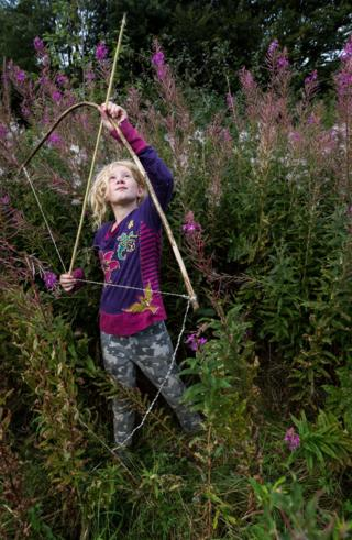 Portrait of Jessica holding a bow and arrow in a meadow