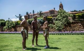 "Khoisan Chief SA (C), Khoisan community members Christian Martin (L) and Brendon Willings (R) talk as they camp during the 12th day, outside the South African government ""Union Buildings"", in Pretoria on December 12, 2017. They were previously refused to enter the buildings by officials who complained about their traditional dress."
