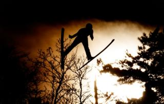 silhouetted figure jumping with skis