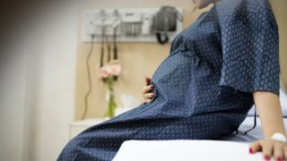 Pregnant woman in a gown sitting on a hospital bed