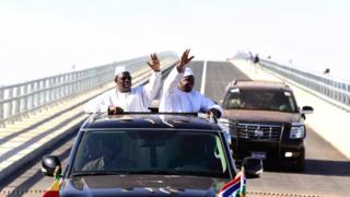 Senegal's President Macky Sall (L) and Gambia's President Adama Barrow (R) wave as they inaugurate a bridge in Farafenni