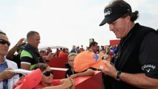 Golfer Phil Mickelson signs an autograph