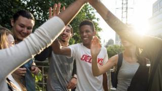 Grupo de adolescentes bate palmas e sorri