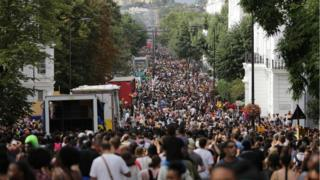 Revellers line the streets on the first day of the Notting Hill Carnival