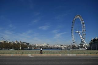 Two police officers walk over a deserted Westminster Bridge with the London Eye seen behind, in central London, 23 March 2020