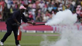 Buthuel Buthelezi, head grounds man, sprays bees on a cricket pitch with a fire extinguisher at the Wanderers stadium in Johannesburg, South Africa, Saturday 4 February 2017