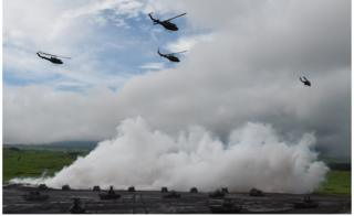 Tanks and helicopters from Japan's Ground Self-Defense Forces, participating in a live fire exercise