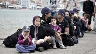 Newly arrived migrants wait their turn to be registered near the port of Mytilene, on the Lesbos island, on June 18, 2015.