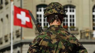 A Swiss soldier stands in front of a Swiss flag