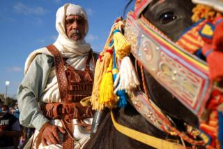 in_pictures A man dressed in ornate, brightly coloured clothes sits astride a horse whose bridle is similarly adorned.