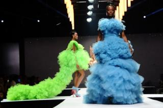 Model wear bright blue and neon green dresses on the catwalk.