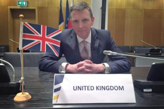Mark Easton with UK flag in Europol boardroom