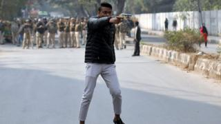An unidentified man brandishes a gun during a protest against a new citizenship law outside the Jamia Millia Islamia university in New Delhi, India, January 30, 2020